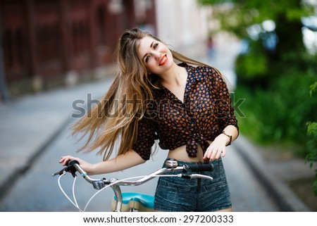 Pretty young girl with long fair hair wearing on blouse and shorts with bicycle having fun on the street   - stock photo
