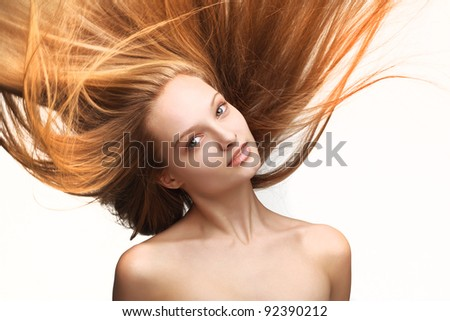 Pretty young girl with long flying hair on white background - stock photo