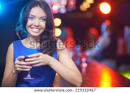 Pretty young girl with martini looking at camera with toothy smile - stock photo