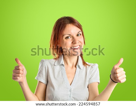 Pretty young girl with thumbs up over green background  - stock photo