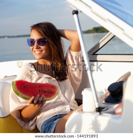 Pretty young girl with watermelon posing on a yacht at a sunny summer day - stock photo