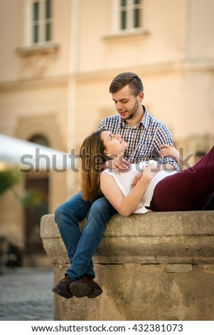 Pretty Young Girlfriend Lying on the Lap of his Handsome Boyfriend While Relaxing at the fountain - stock photo