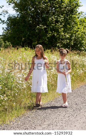Pretty young girls walking next to field of daisies - stock photo