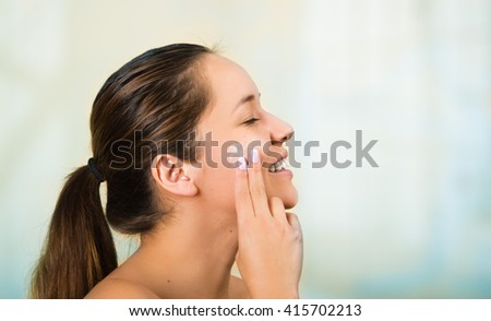 Pretty young healthy hispanic woman headshot with naked shoulders, smiling happily and applying cream to face using hands - stock photo