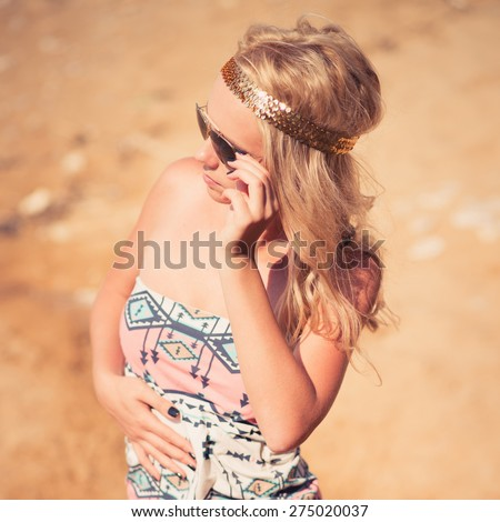 Pretty young hippie caucasian girl, enjoys good weather and the hot sun on a beach. hipster style. Photo with instagram style filters - stock photo