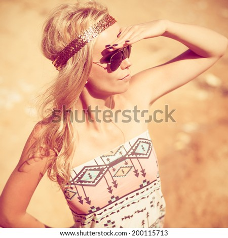 Pretty young hippie caucasian girl, enjoys good weather and the hot sun on a beach. Photo with instagram style filters - stock photo
