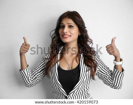 Pretty young Indian girl making thumb up gesture, shows all ok, super, isolated on a white background - stock photo