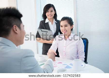 Pretty young lady shaking hands with a male entrepreneur introducing herself or concluding a deal - stock photo