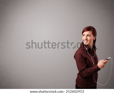 pretty young lady singing and listening to music with copy space - stock photo