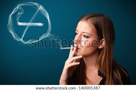 Pretty young lady smoking unheathy cigarette with no smoking sign - stock photo