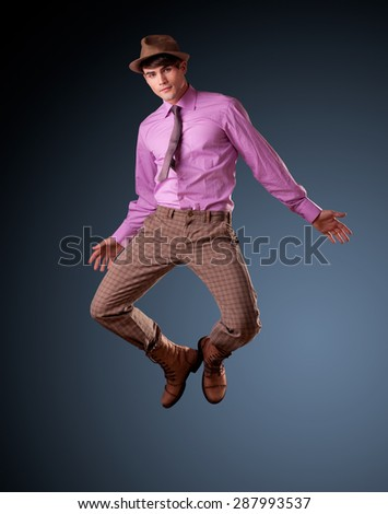 pretty young male model jumping - clean studio shoot, copy space - stock photo