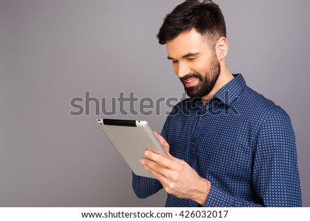 Pretty young man holding tablet and reading news - stock photo