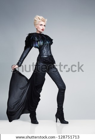 pretty young model wearing futuristic leather clothes standing on a reflective platform an posing on blue background - stock photo