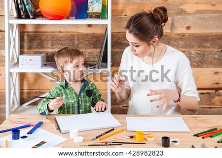 Pretty young mother and his cute little son painting and talking together - stock photo