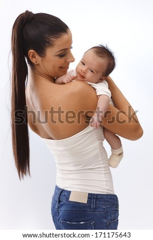 Pretty young mother holding newborn baby in arm, embracing, smiling happy. - stock photo