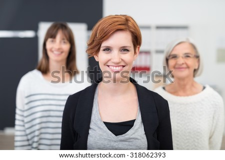 Pretty Young Office Woman Smiling at the Camera Against her Two Female Colleagues - stock photo
