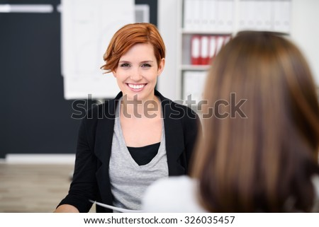 Pretty Young Office Woman Smiling at the Camera While Having a One on One Meeting with her Colleague. - stock photo