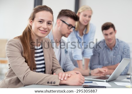 Pretty Young Office Worker in a Meeting at the Boardroom, Looking at the Camera with a Smiling Face. - stock photo