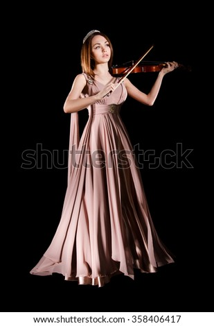 Pretty young playing a violin over black background - stock photo