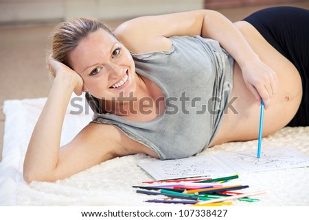 Pretty young pregnant woman drawing with pencils - stock photo