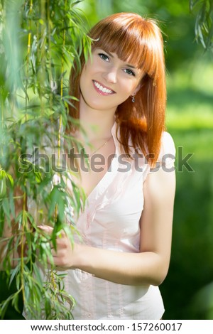 Pretty young red-haired smiling woman posing outdoors - stock photo