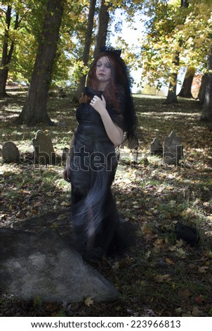 Pretty young red haired woman wearing black veil and standing in the wind in a graveyard - stock photo