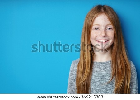 Pretty young redhead girl with an engaging smile standing in front of turquoise blue background with copy space - stock photo