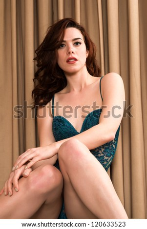 Pretty young redhead in a green bodysuit - stock photo