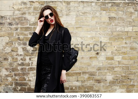Pretty young sexy fashion sensual woman posing on brick wall background dressed in hipster style outfit, stylish fashionable girl with ombre hair in black clothes, travel with backpack. - stock photo