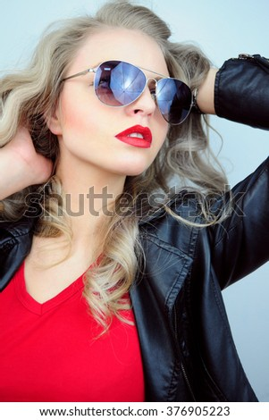 Pretty young sexy fashion sensual woman posing on white wall background dressed in hipster style jeans outfit,Stylish fashionable blonde girl hipster in black clothes. - stock photo
