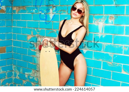 Pretty young sexy woman in black bikini posing in pool on blue background with big longboard desk and have fun in summer  - stock photo