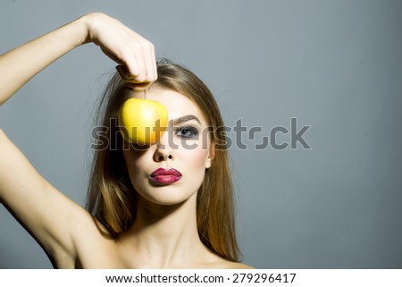 Pretty young sexy woman with bright make up looking forward holding fresh yellow apple covering eye standing on gray background copyspace, horizontal picture - stock photo