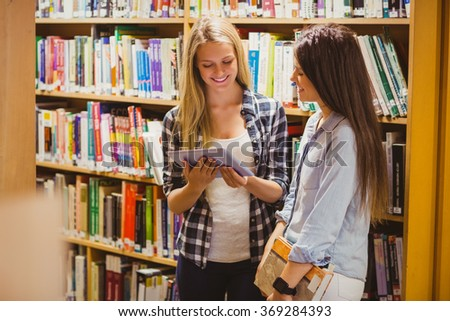 Pretty young students working together with tablet in library - stock photo