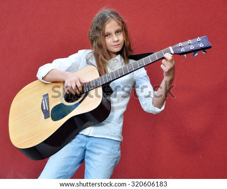 Pretty young teen girl playing acoustic guitar in the street.  - stock photo