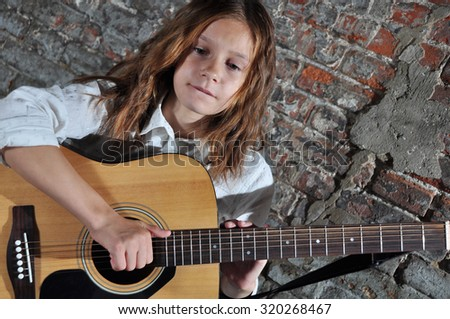 Pretty young teen girl playing acoustic guitar music in the street. Youth music culture concept. - stock photo