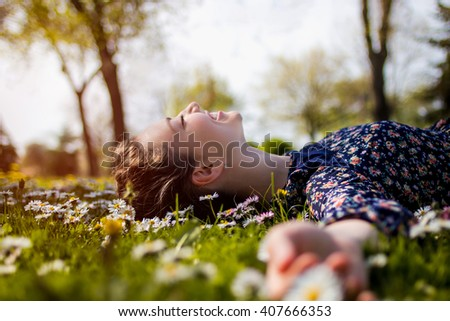 Pretty young teenage girl laying on a grass - stock photo