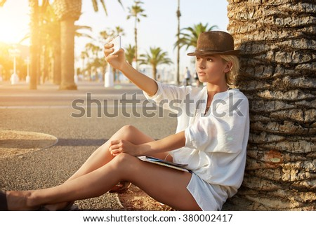 Pretty young tourist making self portrait on mobile phone while sitting near palm tree in sunny day, charming woman photographing herself on cell telephone for social network during summer journey - stock photo