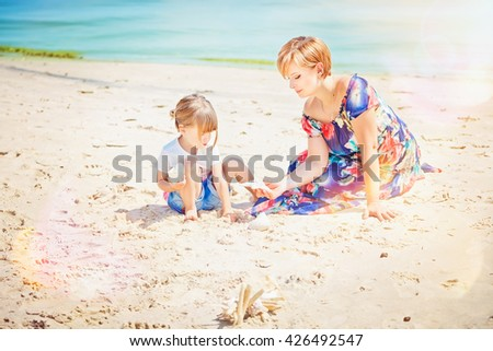Pretty young woman and girl are sitting on the seashore - stock photo