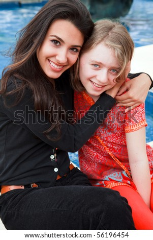 Pretty young woman and girl in a lifestyle pose by a park fountain - stock photo