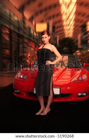 Pretty young woman and red sports car. - stock photo