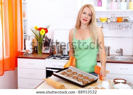 Pretty young woman baking cookies in the kitchen - stock photo