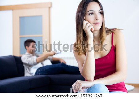 Pretty young woman bored at home while her boyfriend is watching television - stock photo