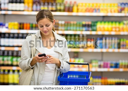 Pretty, young woman buying groceries in a supermarket/mall/gr ocery store (color toned image; shallow DOF) - stock photo