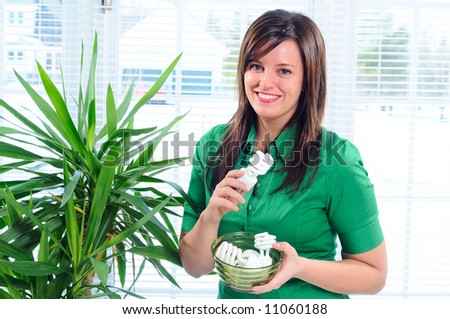 Pretty Young Woman Changing The Light Bulbs In Her Home To Low Energy Compact Fluorescent CFL - stock photo