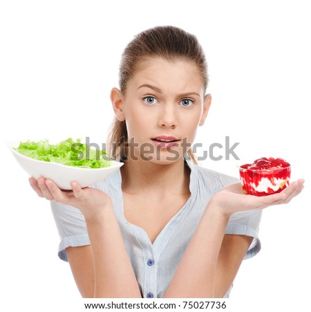 Pretty young woman choice lettuce salad or cake. Isolated on the white background - stock photo