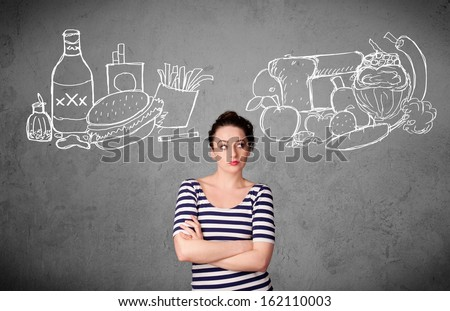 Pretty young woman choosing between healthy and unhealthy foods - stock photo