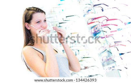 Pretty, young woman choosing new glasses frames in an optician store (color toned image; shallow DOF) - stock photo