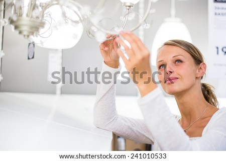 Pretty, young woman choosing the right light for her apartment in a modern home furnishings store (color toned image; shallow DOF) - stock photo