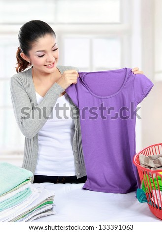 Pretty young woman doing the laundry at home - stock photo