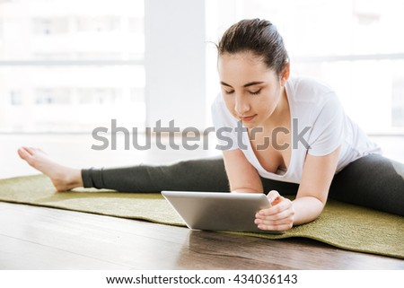 Pretty young woman doing twine and using tablet in yoga studio - stock photo